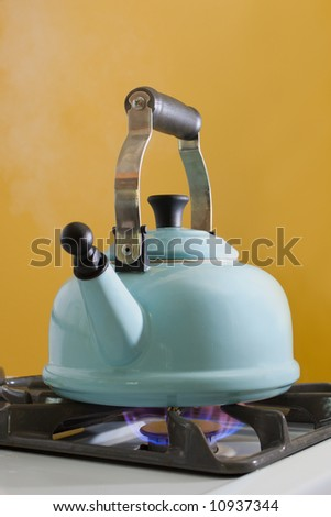 A kettle full of water boiling on a stove top.