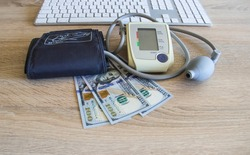 A keyboard with a tonometer and money in dollars lies on the doctor's table. Tonometer with dollars lies on the table in the clinic.