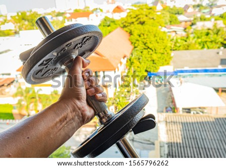 A 4 Kg dumbbell lifted in the air with left hand - it's important to stay fit and healthy - lift weight to lose weight