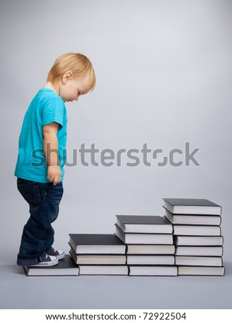 A kid begins his education represented as a steps made of books