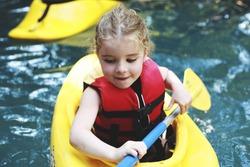 A kid kayaking in beautiful green water