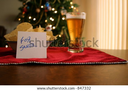 a kid leaves a beer and chips for santa - stock photo