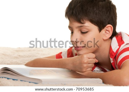 A kid lying on the white carpet is reading a book; isolated on the white background - stock photo