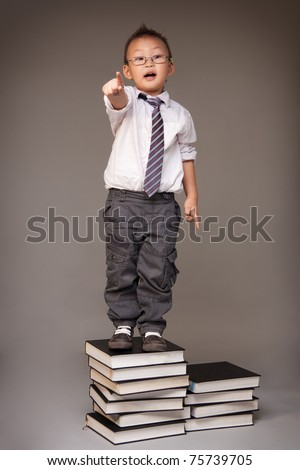 A kid playing a stock trader making a bid standing on pile of books which represents a knowledge