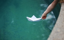 A kid putting a paper boat into water