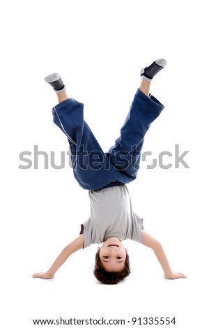 A kid upside down smiling to the camera, looking like a circus artist or maybe a capoeira fighter which is a native Brazilian fight style. Isolated on white.