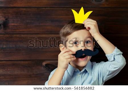 A kid with props for a photo booth. A child with the requisite mustache on wooden background. Event, holiday, party. Copy space.