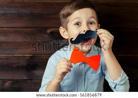 A kid with props for a photo booth. Surprised child with the requisite mustache on wooden background. Event, holiday, party. #561856879