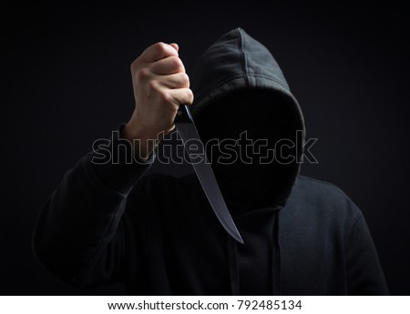 A killer with a knife in his hand in the dark. Attacked the victim Stockfoto ©
