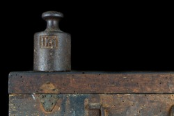 A kilogram weight used for weighing a given quantity in the store. Weights of one kilogram and two kilograms. Dark background.