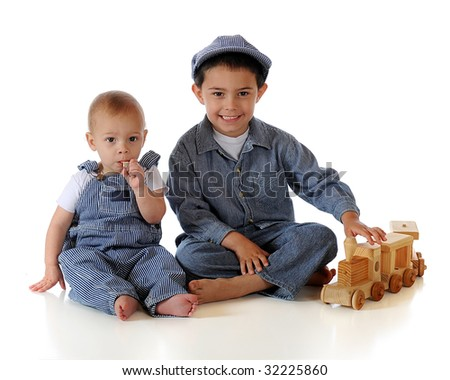A kindergartner and his baby brother dressed as RR engineers while playing with a toy wooden train.  Isolated on white.