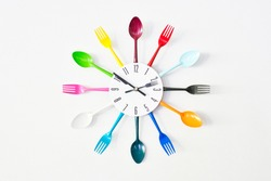 A kitchen wall colorful clock, decorated with bright tableware: spoons and forks