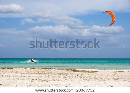 A kite surfer gliding at high speed around the beach Cinta, Sardinia