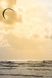 A kite surfer silhouette who sails on a Danish beach at sunset alone. Water sport concept