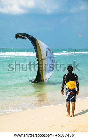 A kitesurfer inspecting a colleagues kite thats about to take off