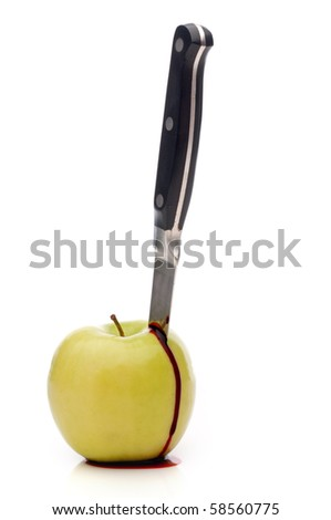 A knife in a bleeding green apple on white
