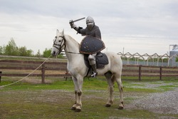 A knight is riding a white horse with a sword in his hand. A man in armor. A model in chain mail. Medieval armor