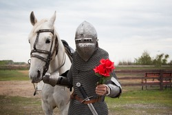 A knight with a white horse and flowers in his hand. A romantic image. A young guy on a horse in medieval armor. Fantasy. Gives roses