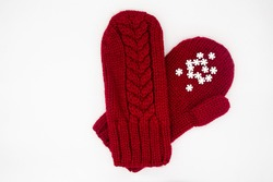 A knitted red mittens with white snowflakes on a white background, isolated. Concept of Christmas, winter, love. Care and Valentine's day. Copy space