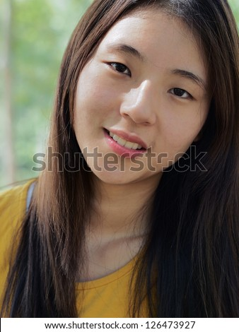 A Korean girl smiling with teeth showing
