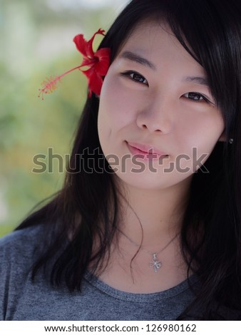 A Korean girl with a red hibiscus on one ear.