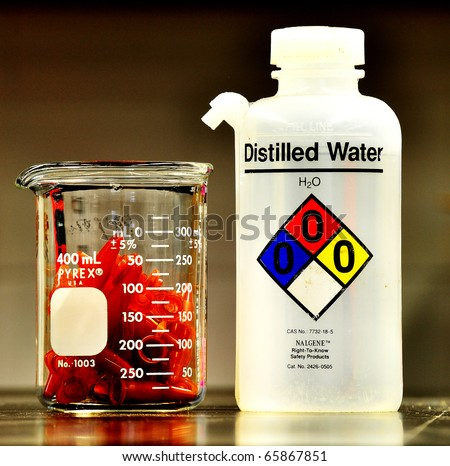 a laboratory distilled water bottle and a pile of eppendorf