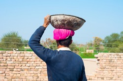 A laborer is carrying cement on his head on the construction site