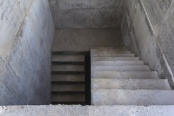 A ladder of concrete leading down. Concrete steps. Stairs down