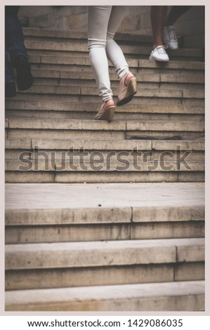 a ladder of white stone, a girl climbs the stairs, legs and stairs, people on the stairs