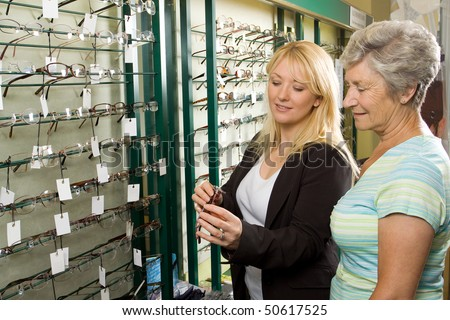 A lady choosing a pair of glasses in an optician