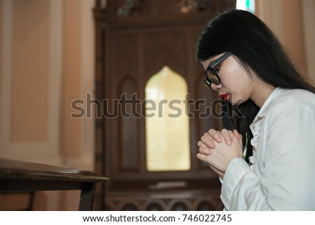 A lady confess for a sin with god, Woman confess for a sin with god, A woman confess for a sin with god in the church, Hands praying in a dark over wooden table, Age 20-30 years, Confessions of Sin