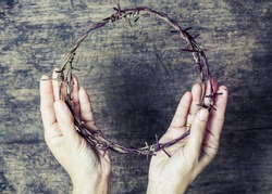 A lady hands holding old metal Barbed Wire made like the crown of thorns of Jesus  can be used for Christian concept , easter concept