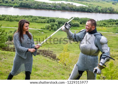 A lady in chain mail and a knight in armor learn to hold a weapon and defend themselves from the blows of a sword. Knightly armor and weapon. Semi - antique photo. #1229315977