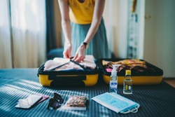 A lady is packing her luggage preparing for a safe travel with face masks and sanitizers.