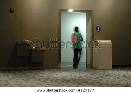 A lady rushing to the washroom (toilet) - stock photo