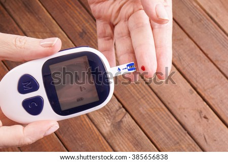 a lady\'s hands measuring blood sugar, glucose with a home test to control her diabetes