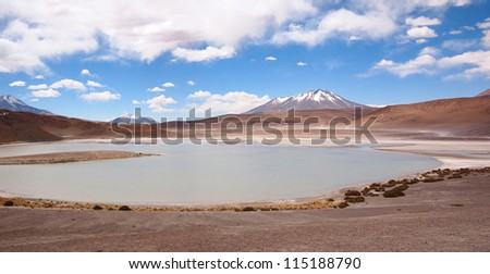 A laguna in Bolivia at the altiplano near Uyuni with a snowcapped volcano in the background.