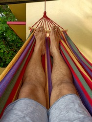 A laid back picture of lazy legs resting on a colorful hammock on a summer afternoon during the Covid19 lock down.