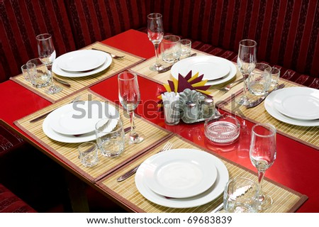 a laid red restaurant table for five persons