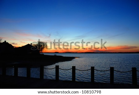 A lake house silhouette during the sunset with deep blue dramatic sky colors. Norman Lake, Northern Carolina, USA.