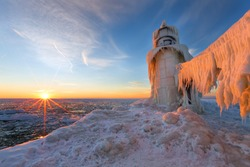 A Lake Michigan winter sunset illuminates the ices that encapsulates the St. Joseph northern pier.