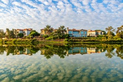 A lake with reflections of buildings and trees in Dubai, UAE under the cloudy sky