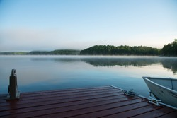 A lakeside dock and fishing boat on an Ontario lake in the morning mist