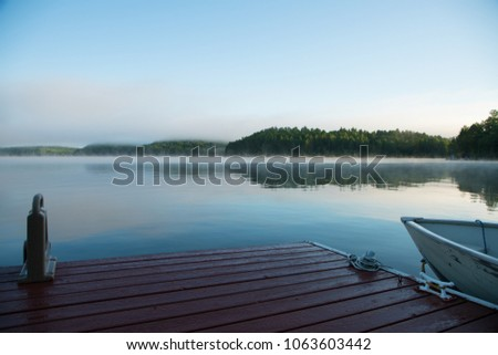 A lakeside dock and fishing boat on an Ontario lake in the morning mist - Shutterstock ID 1063603442