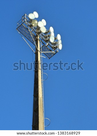 A lamp post with floodlights for a outdoor sport stadium. Cloudless blue sky on a hot day. #1383168929