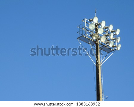 A lamp post with floodlights for a outdoor sport stadium. Cloudless blue sky on a hot day. #1383168932