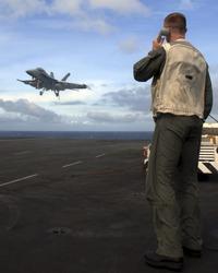 A Landing Signal Officer guides an F-18 Super Hornet aboard an aircraft carrier