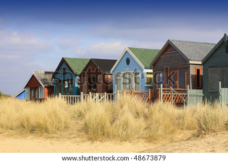 A landscape format image of a row of wooden beach huts with sand grasses to front. Located in Christchurch, Hampshire UK.