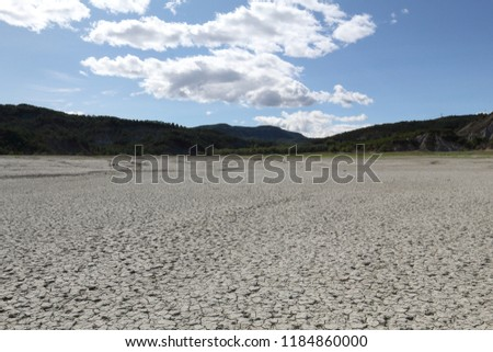 A landscape of a dry cracked grey clay soil during a hot sunny day, with mountains on the background, in the Mediano artifical lake in the Spanish Aragonese Pyrenees