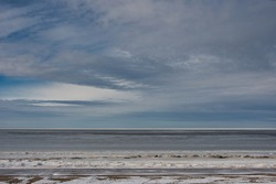 A landscape of a picturesque cloudy sky above the sea, covered with melting grayish watery ice, and a sandy shore with remnants of snow in early spring.